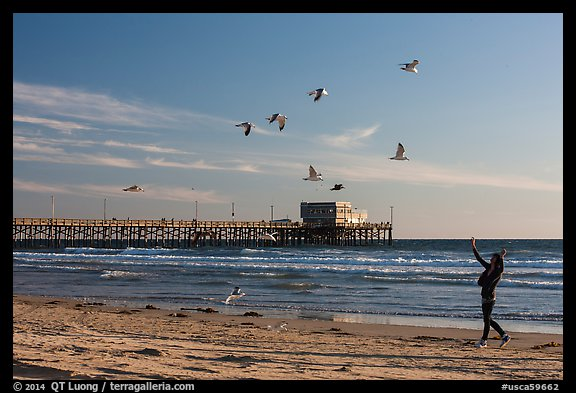Woman and seagulls in front of Newport Pier. Newport Beach, Orange County, California, USA (color)