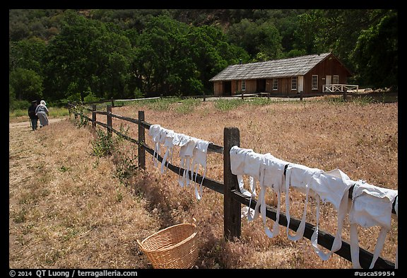 Laundry drying on fence, as elderly couple in period costume walks in distance, Fort Tejon. California, USA (color)