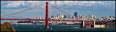 Golden Gate Bridge, and San Francisco city skyline with cloudy sky. San Francisco, California, USA (Panoramic color)