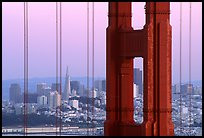 The city seen through the cables and pilars of the Golden Gate bridge, dusk. San Francisco, California, USA