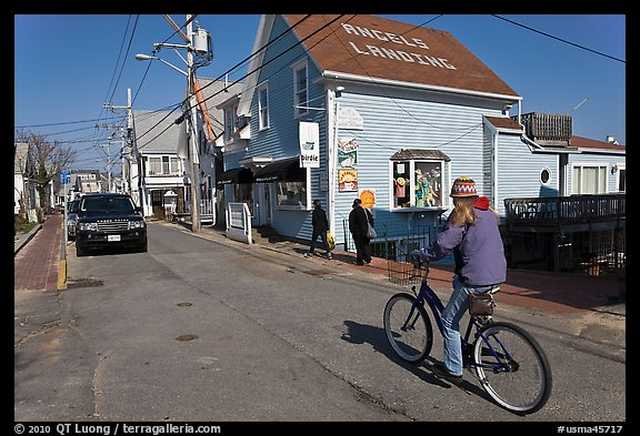 Woman biking on main street, Provincetown. Cape Cod, Massachussets, USA (color)