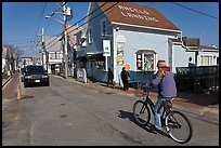 Woman biking on main street, Provincetown. Cape Cod, Massachussets, USA ( color)