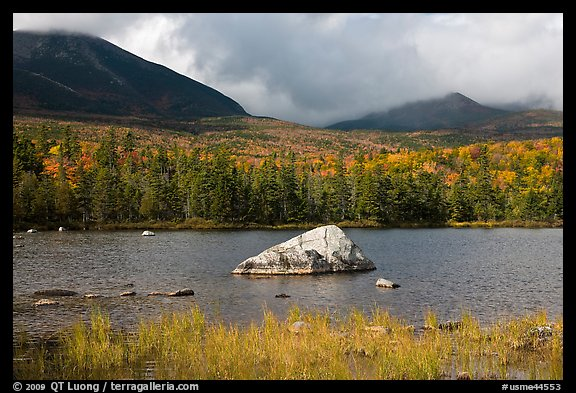 Boulder, pond, forest in autumn and mountains with clouds. Baxter State Park, Maine, USA (color)