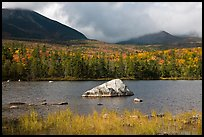 Boulder, pond, forest in autumn and mountains with clouds. Baxter State Park, Maine, USA