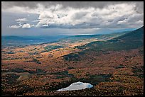 View with storm light and clouds over slopes covered with fall foliage. Baxter State Park, Maine, USA
