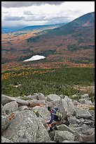 Hiker descends from summit amongst boulders above treeline. Baxter State Park, Maine, USA