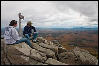 Hikers taking in view near sign marking summit of South Turner Mountain. Baxter State Park, Maine, USA