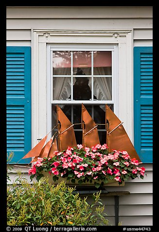 Window with decorative sailboat and flowers. Bar Harbor, Maine, USA