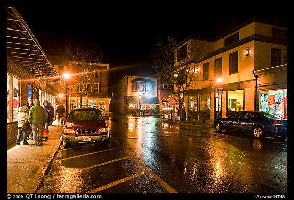 Street at night with people standing on sidewalk. Bar Harbor, Maine, USA (color)