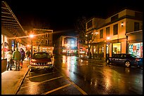 Street at night with people standing on sidewalk. Bar Harbor, Maine, USA