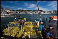 Lobsterman in boat with traps, and village in background. Stonington, Maine, USA ( color)