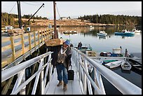 Man carrying construction wood and rolling case out of mailboat. Isle Au Haut, Maine, USA ( color)