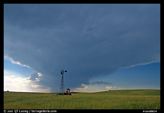 Windmill and tractor under a threatening stormy sky. North Dakota, USA (color)