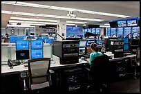 Bloomberg News analyst working in front of many screens. NYC, New York, USA (color)