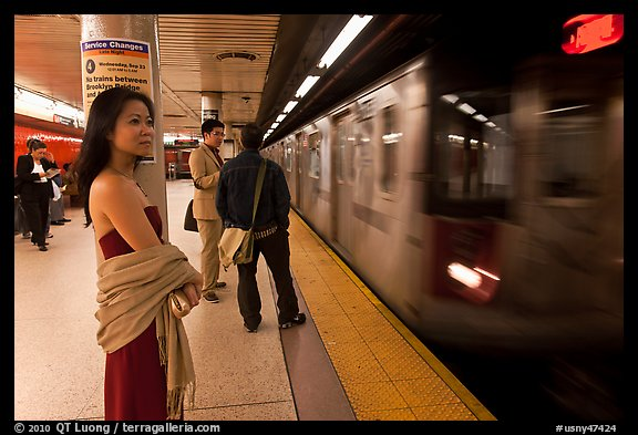 Young woman and arriving train on subway platform. NYC, New York, USA (color)