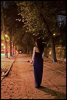 Woman in evening dress with rose on alley bordering Central Park at night. NYC, New York, USA ( color)