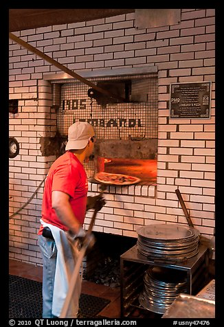 Man loading pizza into oven, Lombardi pizzeria. NYC, New York, USA (color)