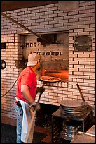 Man loading pizza into oven, Lombardi pizzeria. NYC, New York, USA ( color)