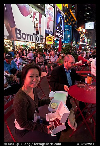 Woman with cupcakes sitting on Times Squares at night. NYC, New York, USA (color)