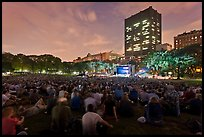 Crowd sitting on lawn during evening outdoor concert, Central Park. NYC, New York, USA (color)