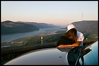 Couple embracing on car hood, with view of mouth of river gorge. Columbia River Gorge, Oregon, USA