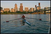 Woman rowing on racing shell and city skyline at sunrise. Portland, Oregon, USA