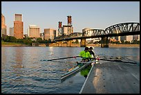 Rowers on double-oar shell lauching from deck in front of skyline. Portland, Oregon, USA
