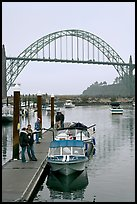 Couple holding small boat at boat lauch ramp. Newport, Oregon, USA ( color)