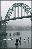 Small boat heading towards ocean under Yaquina Bay Bridge. Newport, Oregon, USA