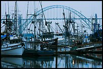 Commercial fishing boats and Yaquina Bay Bridge at dawn. Newport, Oregon, USA (color)