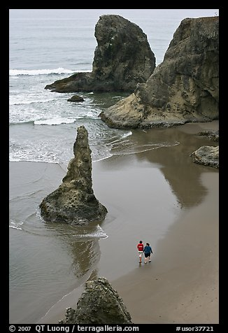 Women walking on beach among rock needles. Bandon, Oregon, USA (color)