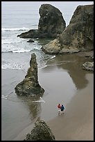 Women walking on beach among rock needles. Bandon, Oregon, USA