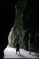 Father and son walking towards the light in sea cave. Bandon, Oregon, USA
