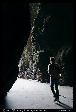 Woman walking out of sea cave. Bandon, Oregon, USA (color)