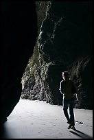 Woman walking out of sea cave. Bandon, Oregon, USA