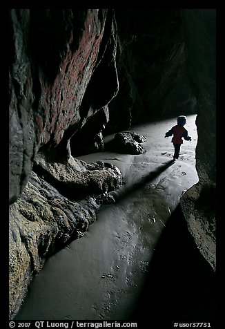 Infant walking out of sea cave. Bandon, Oregon, USA (color)