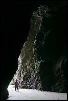 Infant walking into sea cave. Bandon, Oregon, USA