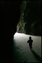 Infant walking towards the light in sea cave. Bandon, Oregon, USA