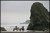 Women ridding horses next to sea stack. Bandon, Oregon, USA (color)