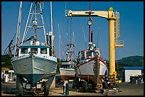 Fishing boats parked on deck with hoist behind, Port Orford. Oregon, USA