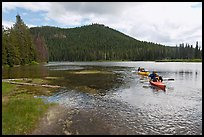 Parents towing children in kayak, Devils Lake. Oregon, USA