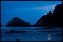Heceta Head and lighthouse beam from beach by night. Oregon, USA