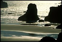 Rocks, water reflections, and beach, late afternoon. Bandon, Oregon, USA