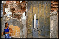 Woman in front of a decaying brick wall, Ponce. Puerto Rico