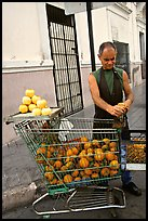 A man peels oranges to make an orange drink, which is drunk from the fruit itself, Ponce. Puerto Rico (color)