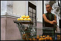 Man peeling oranges to make a drink, drunk from the fruit itself, Ponce. Puerto Rico (color)