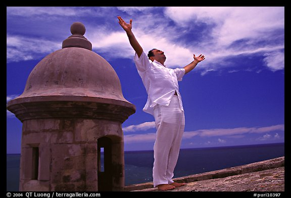 Man standing next to a lookout turret, with arms spread, El Morro Fortress. San Juan, Puerto Rico (color)