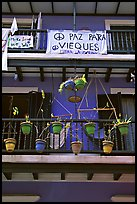 Facade of house painted in blue with plant pots and balconies. San Juan, Puerto Rico