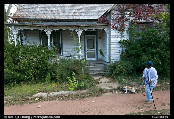 Woman walking dog in front of a crooked house. Selma, Alabama, USA