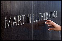 Hand touching the letters Martin Luther King on the Civil Rights Memorial wall. Montgomery, Alabama, USA